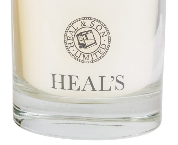 Each candle comes in a glass votive with Heal's insignia.