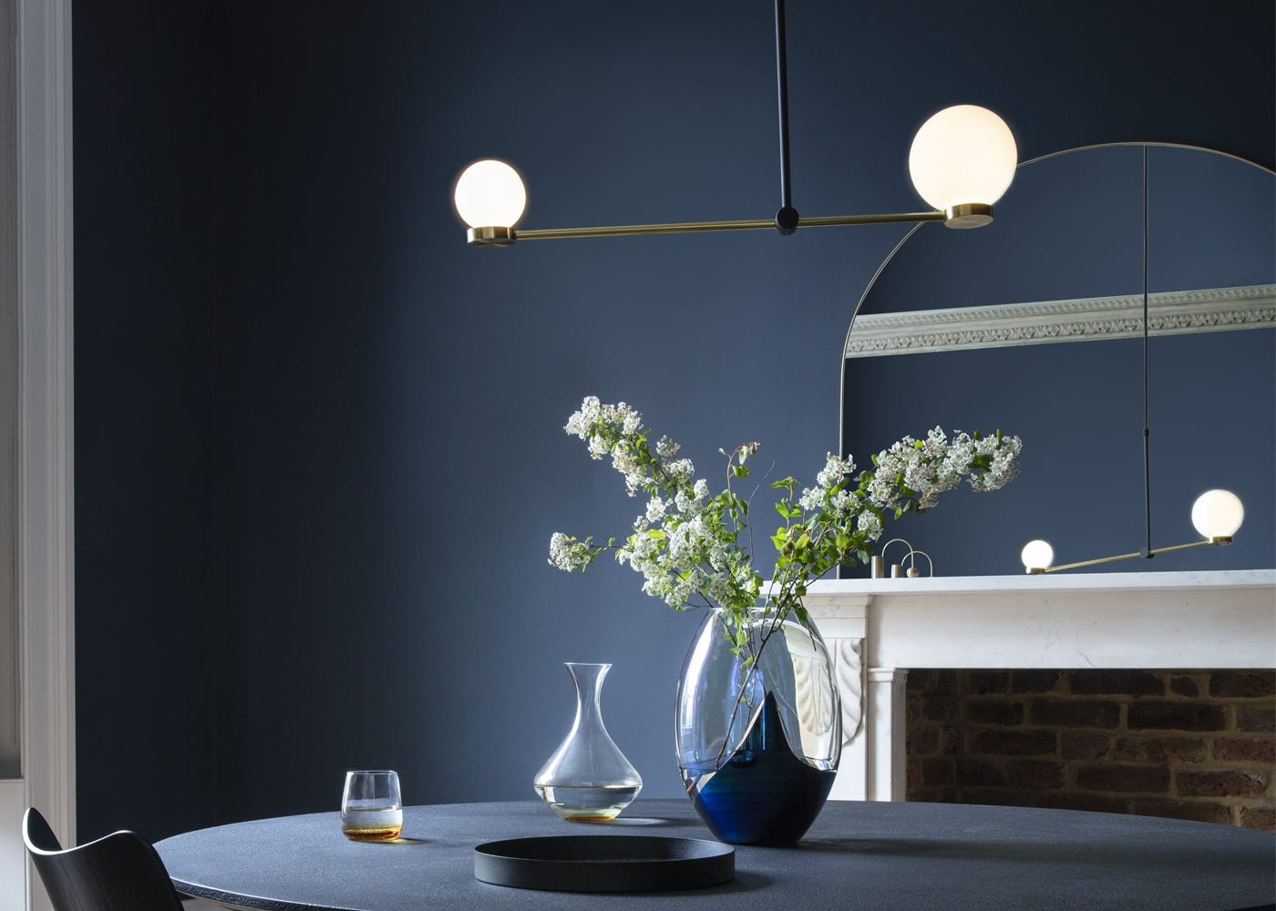 Balance pendant light (on), fine edge over mantel mirror, clay table, slick large vase, antique mirrored tray, amber decanter