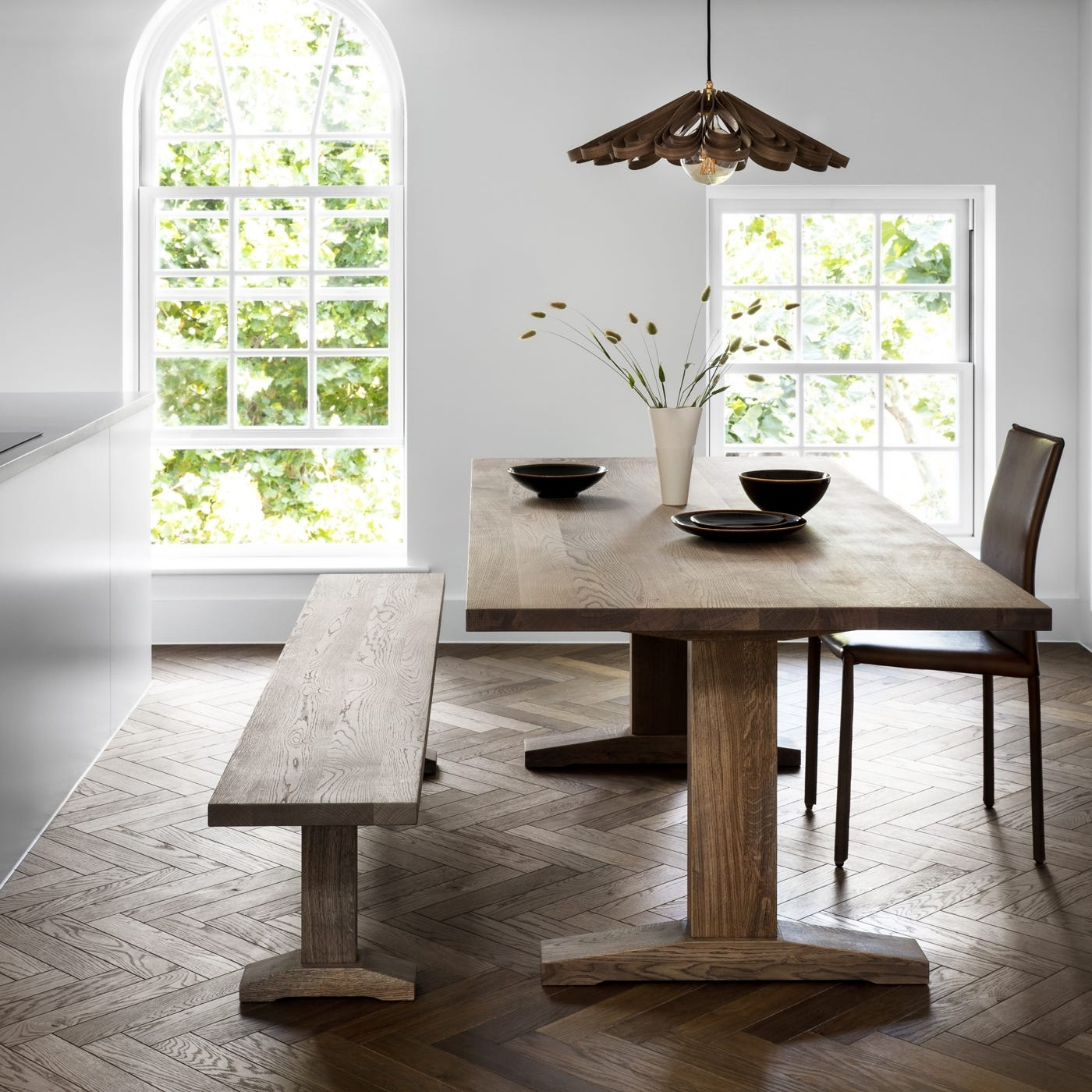 As shown in image: Lisbon dining table in smoked oak, Lisbon bench, Loveramics Studio tableware, Tom Raffield Quill pendant