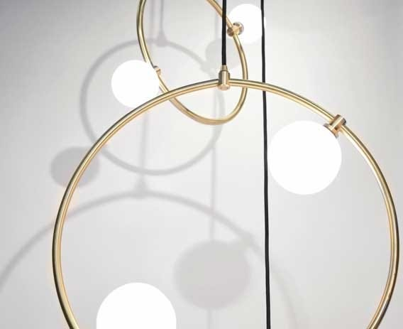 Whitened glass orbs are fastened to delicate brass rings.