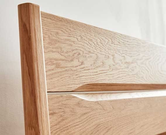 This smooth contemporary understated chamfered planked headboard in pale oak is a signature feature of the Rimini kingsize bed.