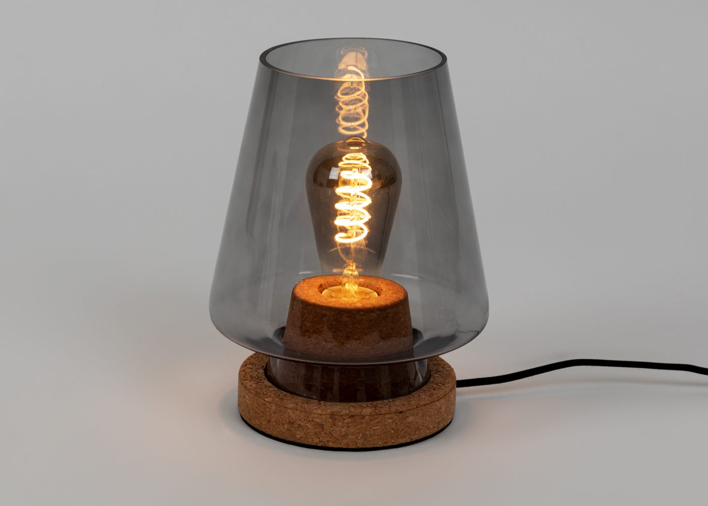 As shown: Arden glass and cork table lamp smoke - On.