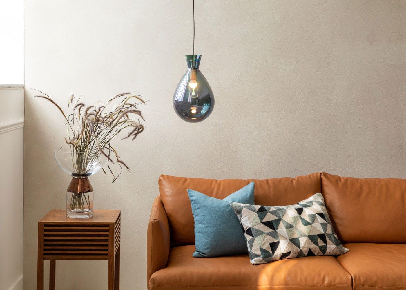 Balloon glass pendant in iridescent smoke, Matera leather sofa, Verona side table in walnut.