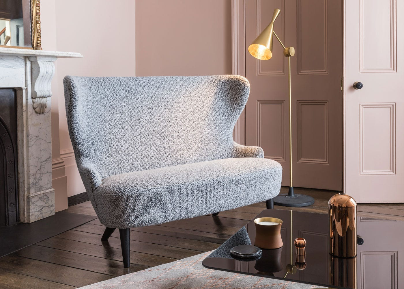 Wingback sofa paired with beat floor lamp in brass.