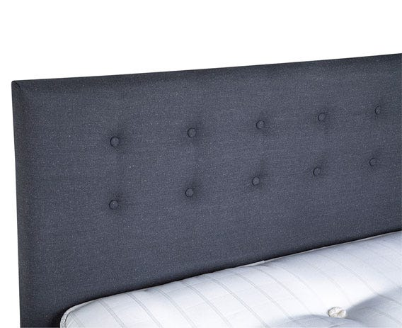 A solid dark wooden frame is paired with a smokey grey fabric headboard.