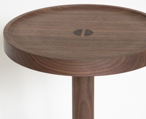 Crafted from solid walnut with a circular top that features a raised edge.