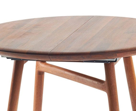 This solid walnut round table boats a beautifully concealed leaf.