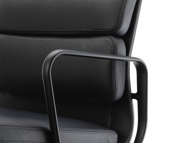 The sewn on leather cushions creates a striking contrast to the slender aluminium profile.