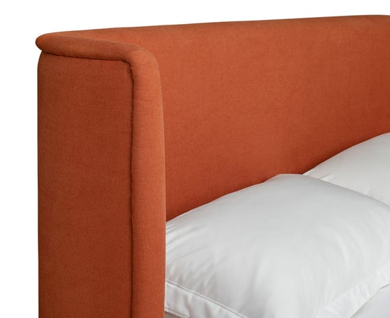 Curved headboard wraps around the head of the mattress to give a cosy feel