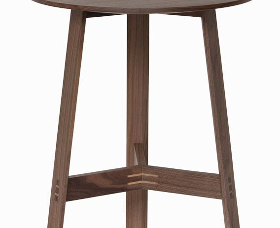 The three broad table legs have chamfered inside edges which catch the light and create a slim silhouette.