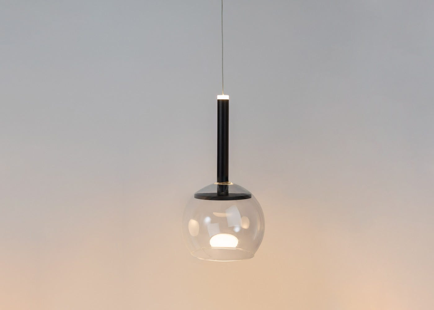 As shown: Disc long LED pendant in black with clear glass shade (sold separately) - on.