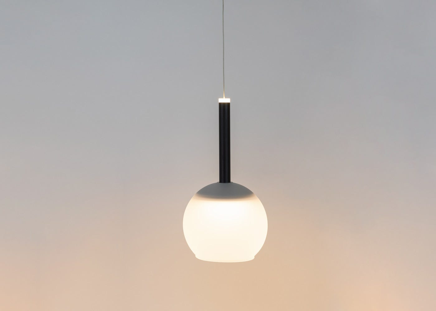 As shown: Disc long LED pendant in black with frosted glass shade (sold separately) - on.