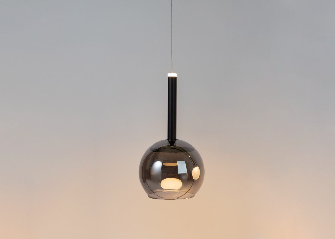 As shown: Disc long LED pendant in black with smoked glass shade (sold separately) - on.