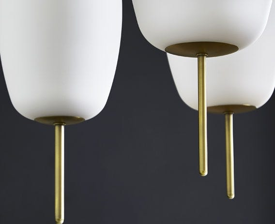 The light is balanced by the architectural brass stems found at the top and bottom.