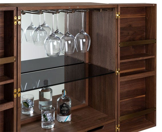 The drinks cabinet features a luxurious interior; with ample space for bottles, glasses and accessories. Featuring brass plated details and a mirrored back panel.